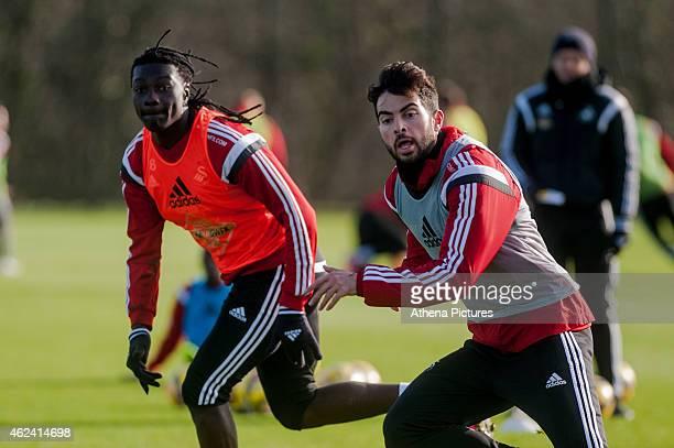 Bafetimbi Gomis and Jordi Amat of Swansea City run forwards during training on January 28 2015 in Swansea Wales