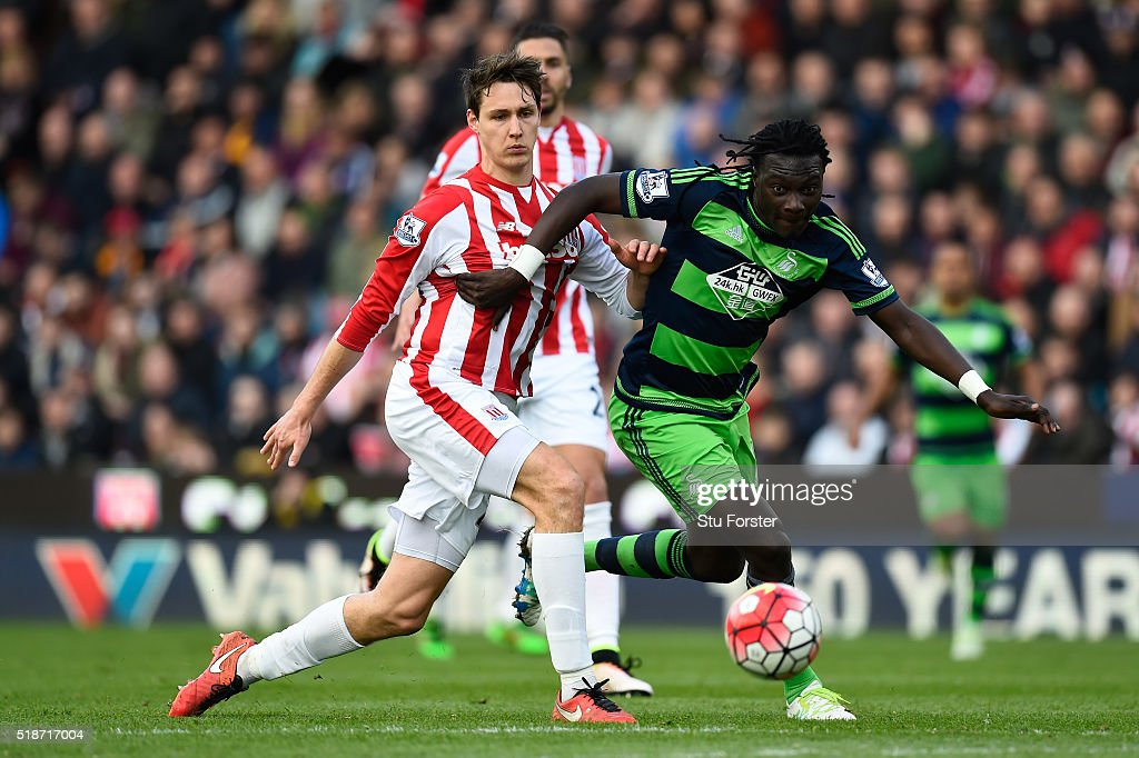 Bafetimbi Gomis of Swansea City and Philipp Wollscheid of Stoke City compete for the ball during the Barclays Premier League match between Sstoke City and Swansea City at Britannia Stadium on April 2, 2016 in Stoke on Trent, England.