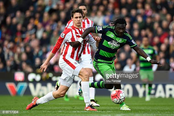 Bafetimbi Gomis of Swansea City and Philipp Wollscheid of Stoke City compete for the ball during the Barclays Premier League match between Sstoke...