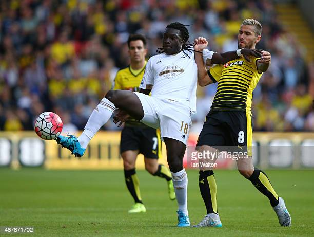 Bafetimbi Gomis of Swansea City is challenged by Valon Behrami of Watford during the Barclays Premier League match between Watford and Swansea City...
