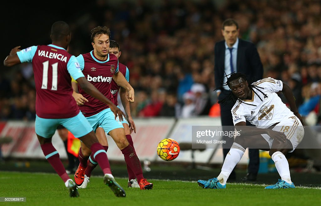 Bafetimbi Gomis of Swansea City is closed down by Enner Valencia and Mark Noble of West Ham during the Barclays Premier League match between Swansea City and West Ham United at the Liberty Stadium on December 20, 2015 in Swansea, Wales.