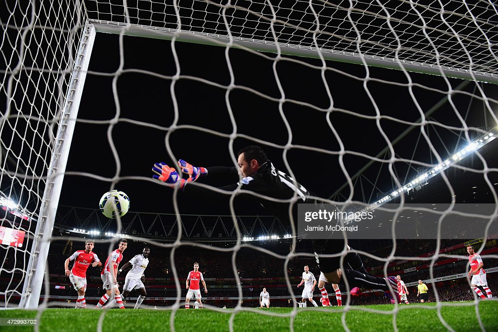 Bafetimbi Gomis of Swansea City scores the first goal as goal line technology rules the ball to cross the line depsite David Ospina of Arsenal making a save during the Barclays Premier League match between Arsenal and Swansea City at Emirates Stadium on May 11, 2015 in London, England.