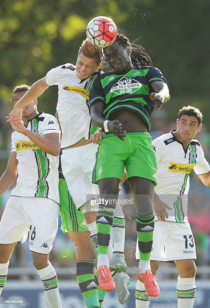 Bafetimbi Gomis of Swansea is challenged by Nico Elvedi of Borussia Moenchengladbach during the City Preseason Friendly between Borussia Moenchengladbach and Swansea at Grassau on July 15, 2015 in Grassau, Germany.