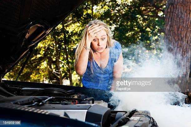 Baffled blonde is frustrated by her car's smoking engine
