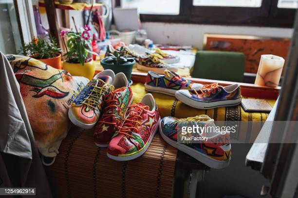 bag and bunch of sneakers painted in a abstract way - multi colored shoe stock pictures, royalty-free photos & images