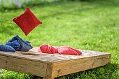 Bag flying onto corn hole board in backyard