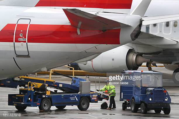 A bag handler unloads the belly of an American Airlines jet at Boston Logan International Airport in Boston on April 24 2020