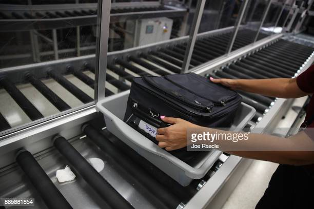 A bag is cleared through an automated screening lane funded by American Airlines and installed by the Transportation Security Administration at Miami...