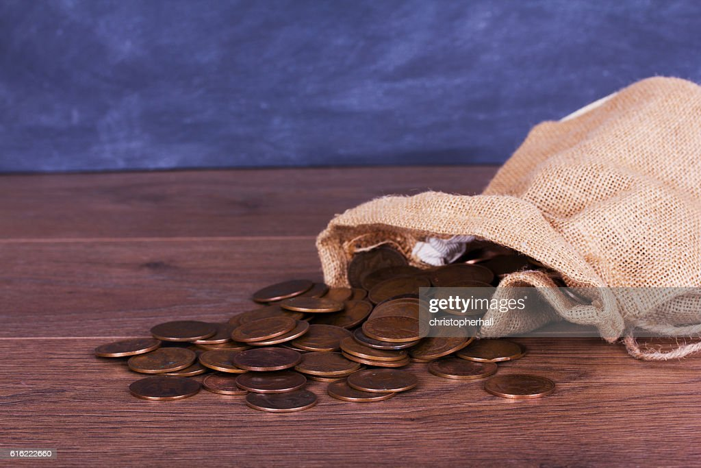 Bag of coins spilt over a wooden surface : Bildbanksbilder
