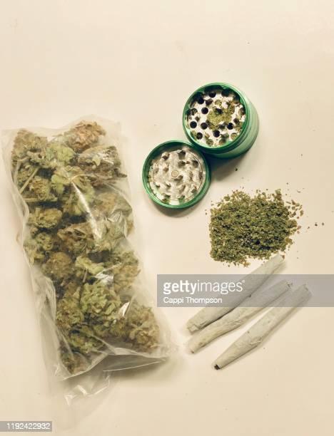 bag of dried cannabis sativa rolled joints, ground herb, and grinder - opgerold samenstelling stockfoto's en -beelden