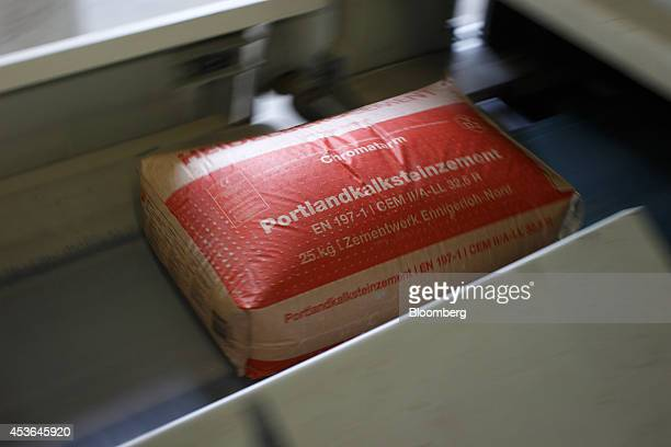 A bag of Portland cement passes along the production line at HeidelbergCement AG's plant in Ennigerloh Germany on Friday Aug 15 2014 HeidelbergCement...
