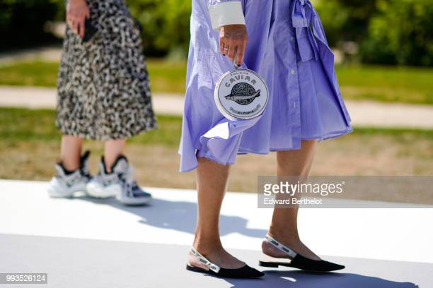 A bag shaped as a Caviar box a purple pleated skirt Dior shoes outside Dior during Paris Fashion Week Haute Couture Fall Winter 2018/2019 on July 2...