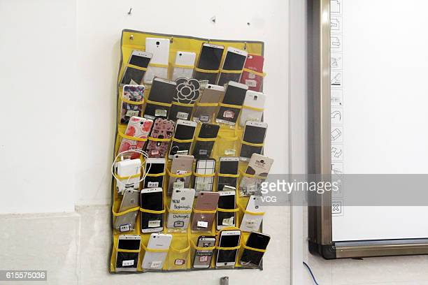A bag storing students' mobile phones hangs next to the blackboard in a classroom of a vocational and technical school at Tonglu County on October 19...