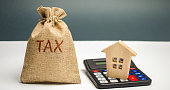 A bag with the word Tax and calculator with a house. Taxes on real estate, payment. Penalty, arrears. Register of taxpayers for property. Law-abiding, evasion of payment. Court law. Luxury tax