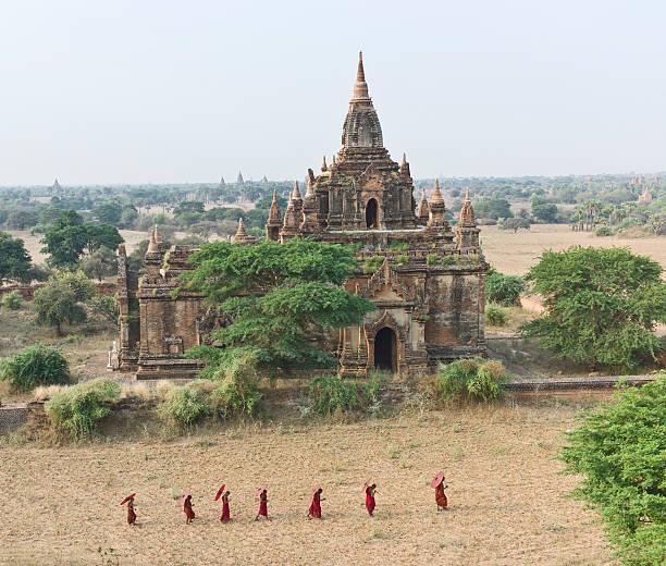 Bagan, Buddhist monks walking past temple