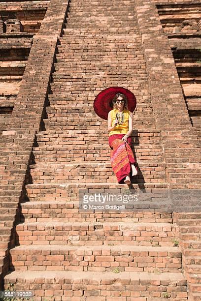 Bagan, Mandalay region, Myanmar (Burma). Caucasian tourist girl sitting on the stairs of a stupa in Bagan.