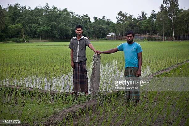 Bagdakia Indian enclave resident Mohammad Anwar Hossain stands in Indian territory while Bangladeshi citizen Mohammar Monwar Hossain stands in...