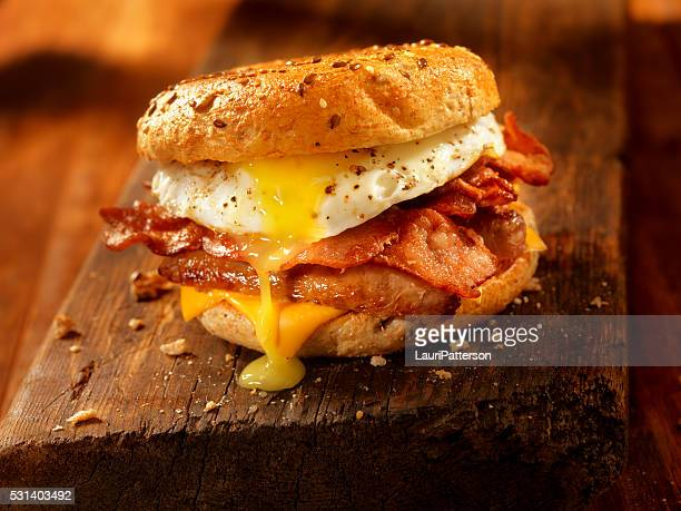 bagel, bacon, sausage and egg breakfast sandwich - sandwich stock pictures, royalty-free photos & images