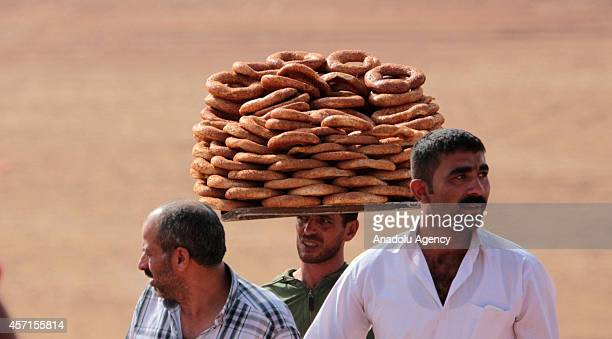 A bagel dealer sells bagels as residents of Suruc district at the TurkishSyrian borderline watch the airstrikes of USled coalition against the...