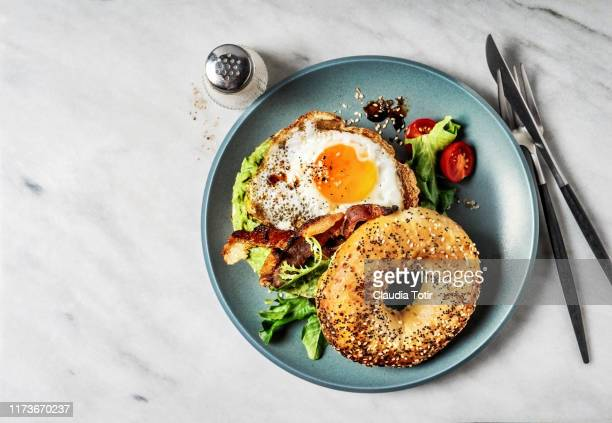 bagel sandwich with avocado, fried egg and side salad on white background - prima colazione foto e immagini stock