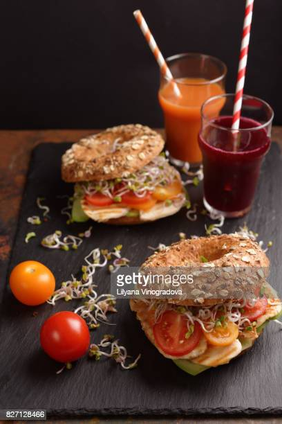 Bagel sandwich with chicken, tomato, radish sprouts, cucumbers and vegetable juices