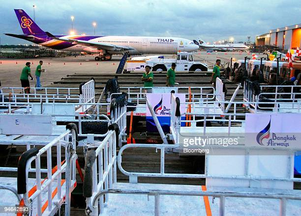 Baggage carts and aircraft movers are loaded on trucks on the last day of operations at Bangkok's old Don Muang airport before the move to the new...