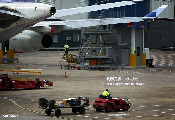 A baggage handler at Sydney International Airport drives luggage across the tarmac 13 May 2005 SMH Picture by JON REID