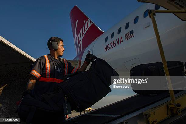 A baggage handler loads a luggage onto a Virgin America Inc Airbus A320 plane on the tarmac at San Francisco International Airport in San Francisco...