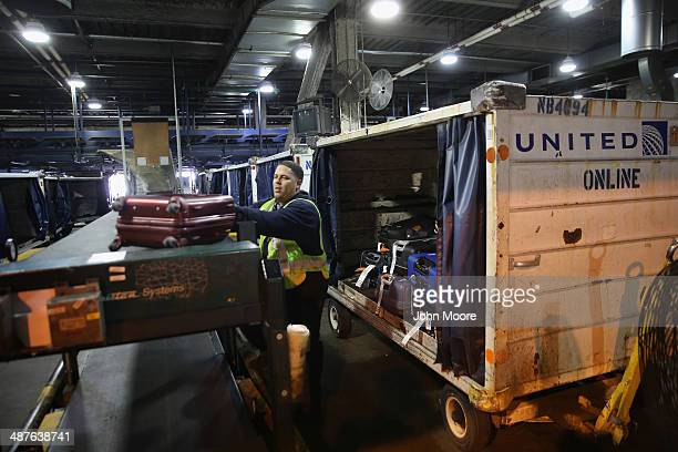 A baggage handler loads luggage after it was screened in a new explosives detection system at the Newark Liberty International Airport on May 1 2014...