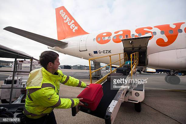 A baggage handler loads passenger's luggage onto an Airbus A319 aircraft operated by EasyJet Plc before take off from the airline's hub at London...
