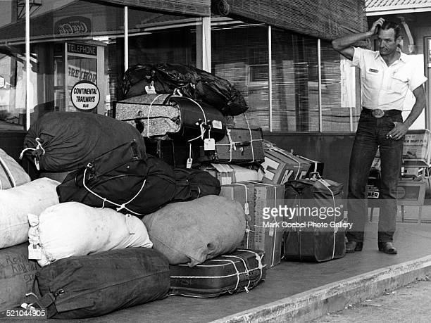 Baggage handler looking at pile of luggage May 1965