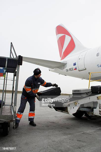 A baggage handler places passenger luggage onto a conveyor belt during the loading of an Airbus A319 aircraft operated by Ceske Aerolinie AS airline...