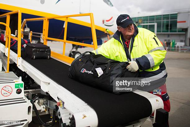 A baggage handler takes luggage from conveyor belt connected to a Ryanair Holdings Plc passenger aircraft at Stansted Airport operated by Manchester...