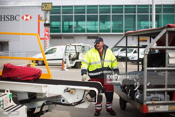 A baggage handler watches luggage on a conveyor belt as it comes off a Ryanair Holdings Plc passenger aircraft at Stansted Airport operated by...