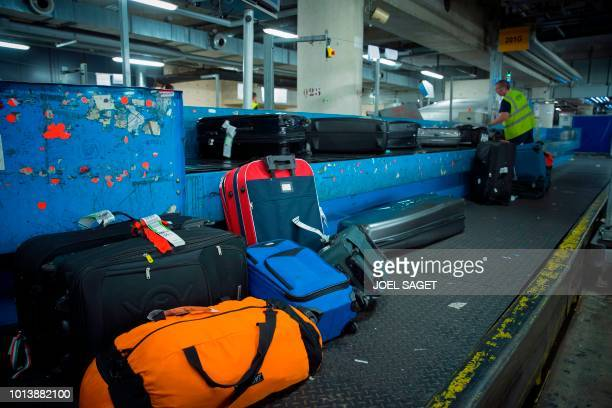 A baggage handler works in a baggage sorting centre at the RoissyCharles de Gaulle airport in RoissyenFrance north of Paris on August 8 2018