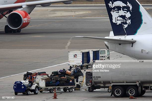 Baggage handlers load an Alaska Airlines jet at Los Angeles International Airport as the airline plans to cut capacity and slash jobs on September 12...
