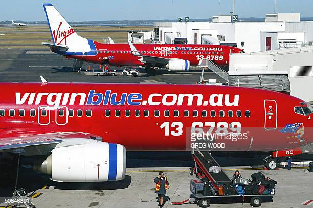 Baggage handlers load luggage onto a passenger jet from Australian budget airline Virgin Blue as it is prepared for a flight at Sydney Airport 17 May...