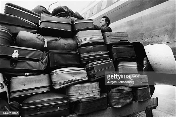 Baggage handlers loading suitcases at Luton Airport UK 1965