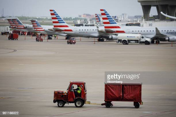 Baggage is transported on the tarmac past American Airlines Group Inc planes at DallasFort Worth International Airport in Grapevine Texas US on...