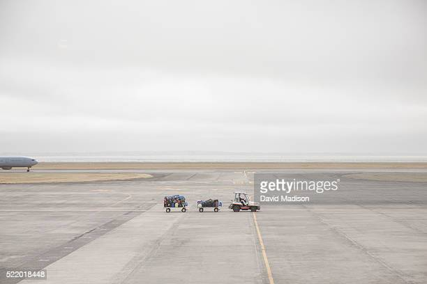 Baggage wagons and plane on airport runway, Auckland, North Island, New Zealand
