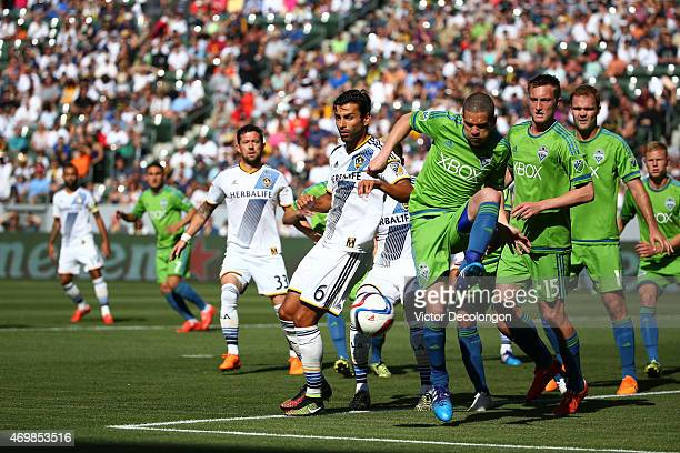 Baggio Husidic of the Los Angeles Galaxy looks on as Osvaldo Alonso of Seattle Sounders FC clears the ball from a corner kick in the first half of...