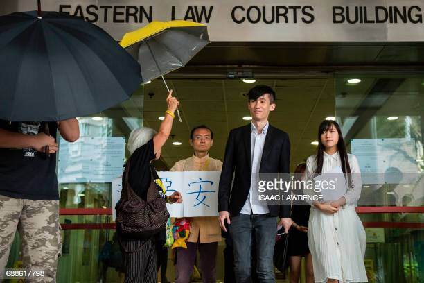 Baggio Leung and Yau Waiching from localist political group Youngspiration leave a court in Hong Kong on May 26 after they pleaded not guilty to...