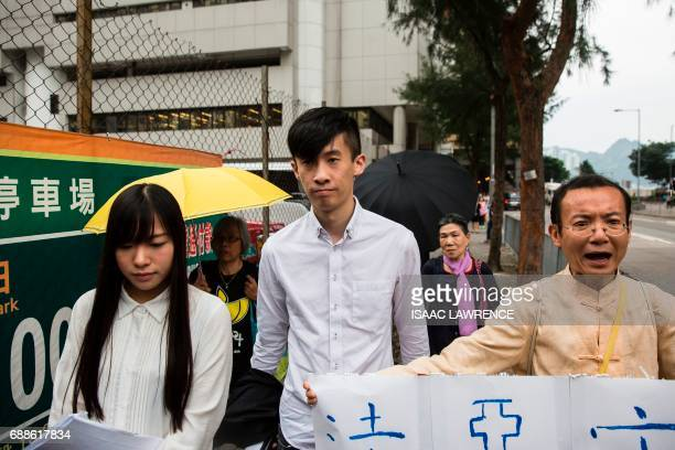 Baggio Leung and Yau Waiching from localist political group Youngspiration walk with supporters as they leave a court in Hong Kong on May 26 after...