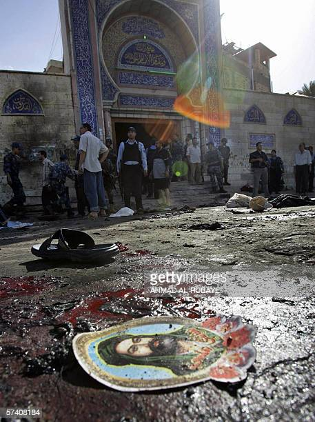 A poster bearing the image of Imam Ali cousin of the Prophet Mohammed lies in a pool of blood outside the Baratha mosque in Baghdad 07 April 2006...