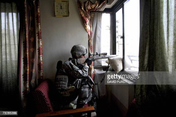 A US Army sniper from Bravo Company 520 Infantry Regiment provides overwatch from an Iraqi home in the Adamiyah neighbourhood of northern Baghdad...