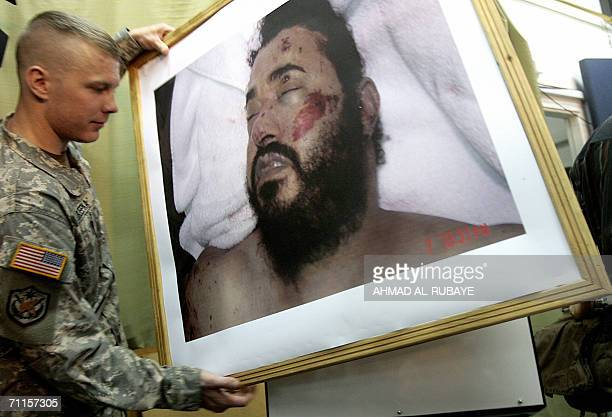 A US soldier carries a picture of alQaeda leader in Iraq Abu Musab alZarqawi during a US military briefing 08 June 2006 in Baghdad The image shows...
