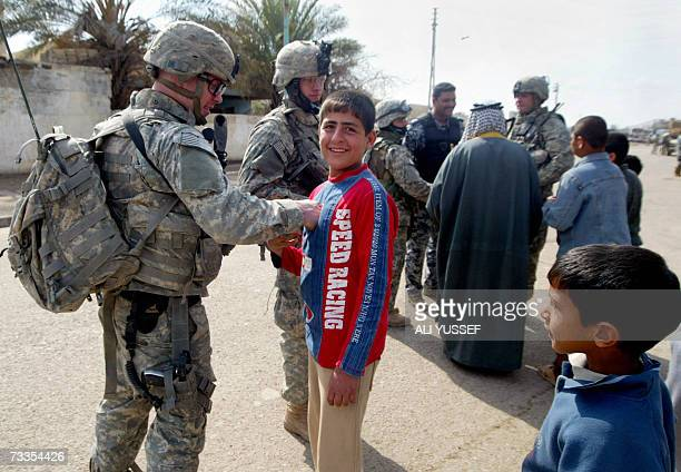 A US soldier shares a moment with an Iraqi boy during a patrol at an area northeast of Baghdad 17 February 2007 Attacks and killings in the war torn...