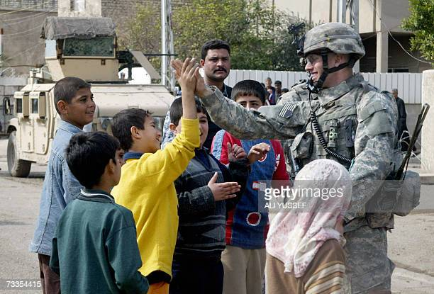 A US soldier shares a moment with Iraqi children during patrol at an area northeast of Baghdad 17 February 2007 Attacks and killings in the war torn...