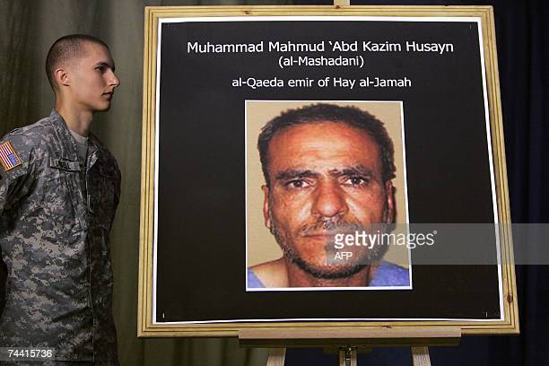 A US soldier stands next to a portrait for AlQaeda Emir Mohammed Mahmud 'Abd Kadhim Hussein alMashadani during a press conference for Brigadier...