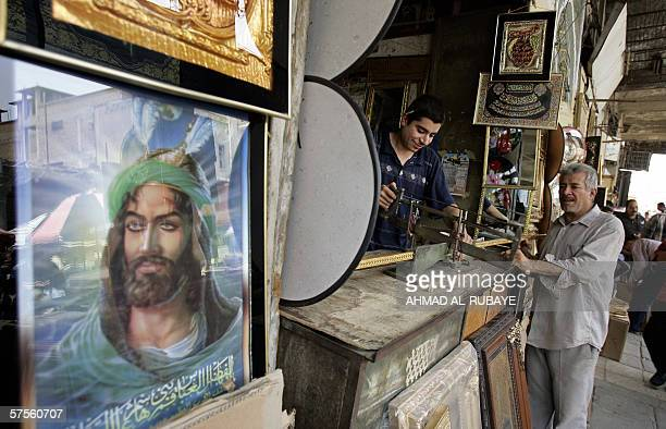 An image of Shiite Imam Abbas son of Imam Ali adorns the side of a shop as an Iraqi craftsman assembles a frame in Baghdad 09 May 2006 Iraq's Prime...